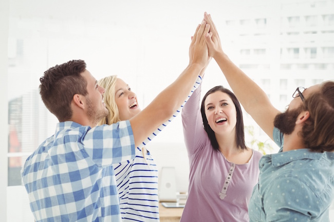 Smiling business people giving high five