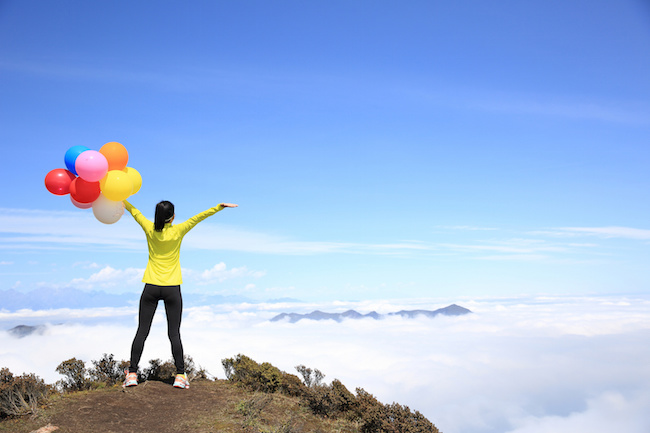 cheering young woman with colorful balloons on mountain peak