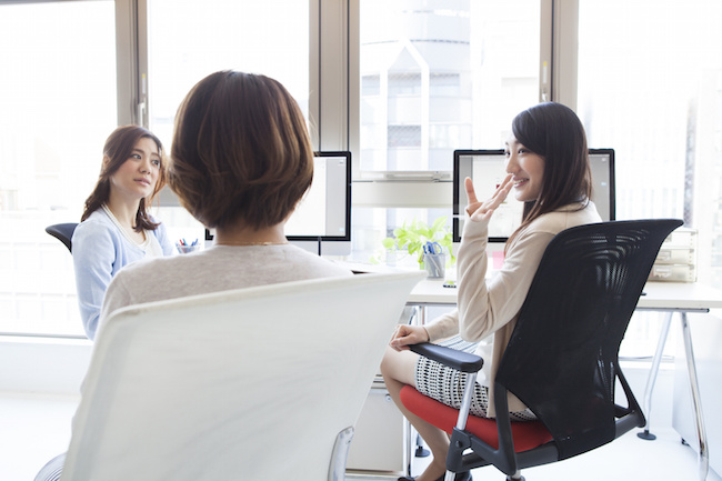 Three business women are chatting in the office