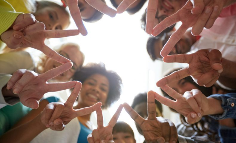 education, friendship, gesture, victory and people concept - group of happy international students or friends standing in circle and showing peace or v sign