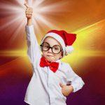Kind mit Weihnachtsmütze hält Daumen hoch bei der Weihnachtsfeier