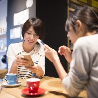 Women who are looking at the mobile phone in a cafe