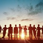Silhouette of business people of different professions on sunset background